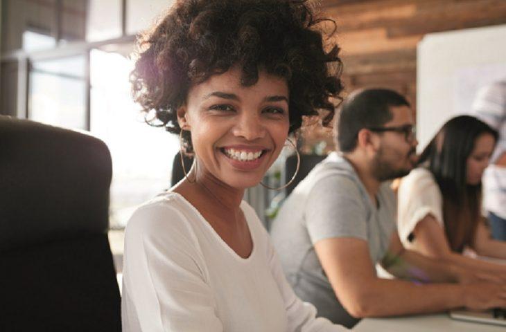 Jeune femme souriante au bureau, santé des actifs