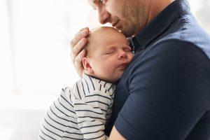 Papa serrant dans ses bras un bébé nourrisson