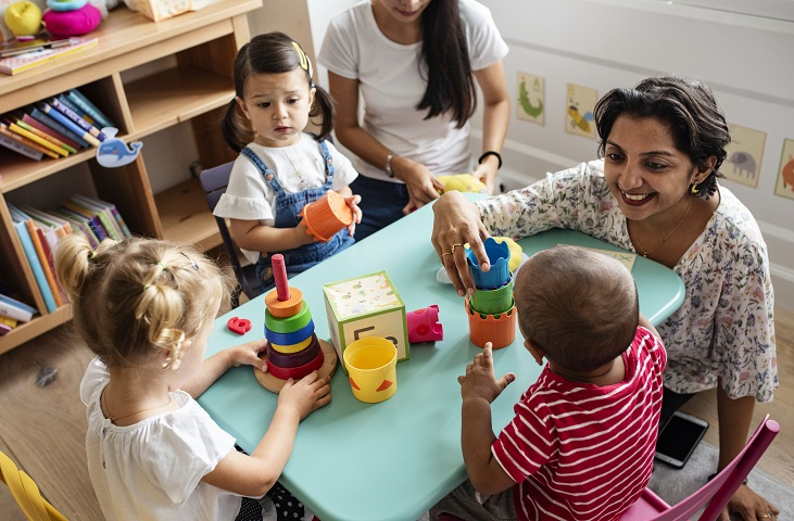 Une assistante maternelle joue avec des jeunes enfants
