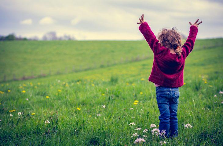 Enfant levant les bras dans un pré verdoyant